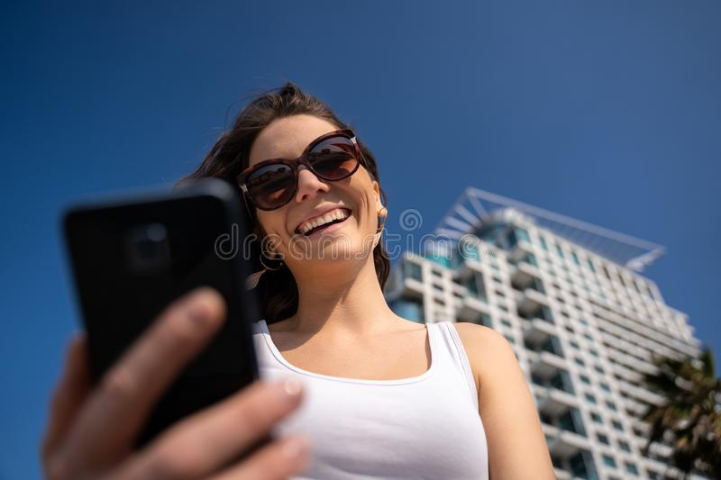 Young woman using the phone. City Skyline In Background. Woman smiling and using a smartphone in the city, clear sky and tall buildings as background royalty free stock images
