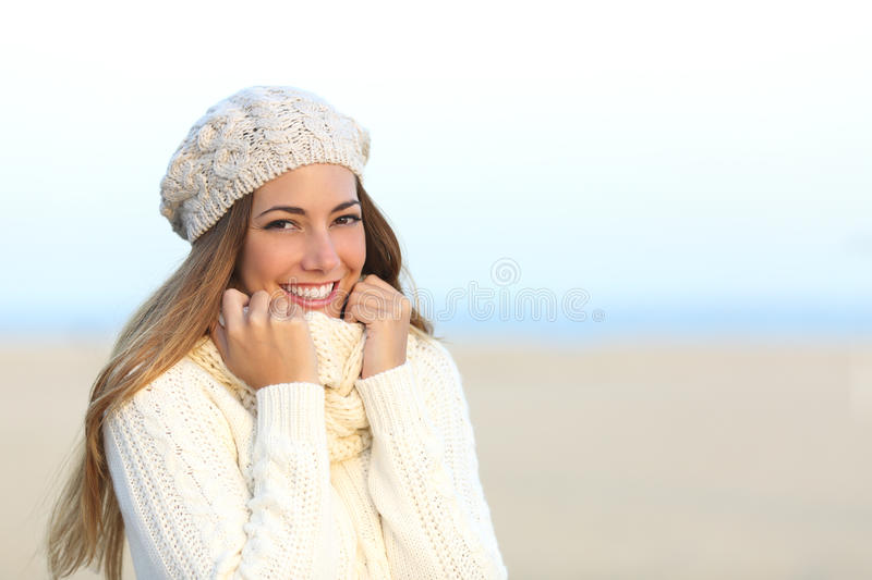 Woman smiling warmly clothed in winter. Woman smiling warmly clothed in a cold winter on the beach royalty free stock image