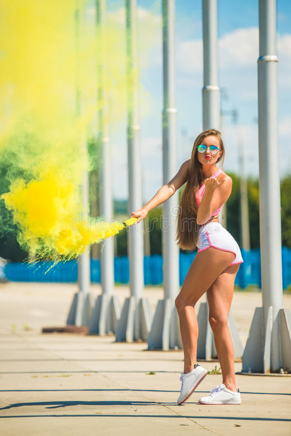Woman with smoke bomb. Joyful young woman is holding smoke bomb and blowing a kiss outdoor stock photo
