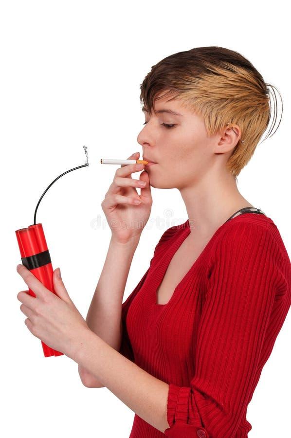 Woman smoker. Beautiful woman lighting a cigarette with dynamite stock image