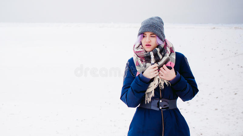 Woman smokes an electronic cigarette in the street near the snow-covered river. Vaping girl. winter street portrait of a woman hipster, purple-dyed hair, a gray stock images