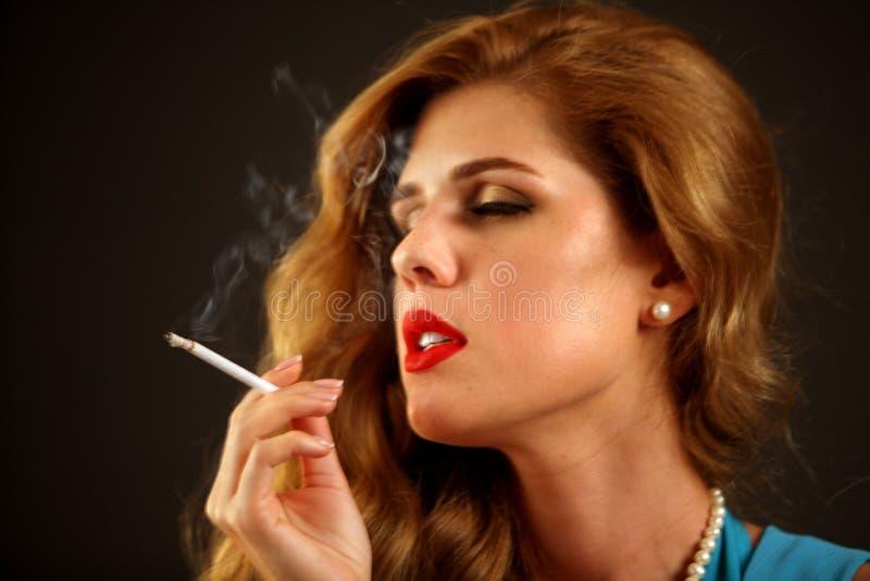 Woman smokes marijuana. Girl who smokes cigarette. Smoke is bad habit. Nicotinic acid is harmful to health and female beauty. Female dreems quit smoking royalty free stock photo