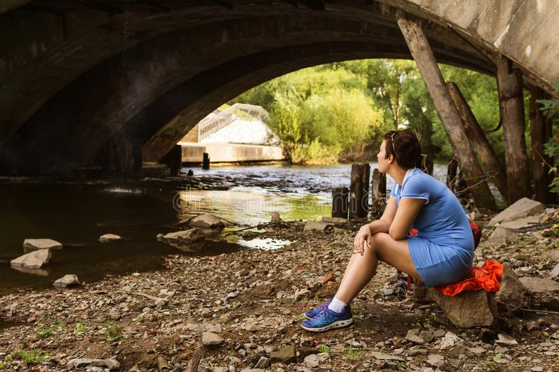 Woman smokes while sitting alone under a bridge. Woman smokes while sitting alone under an old bridge on the banks of a city river royalty free stock photo