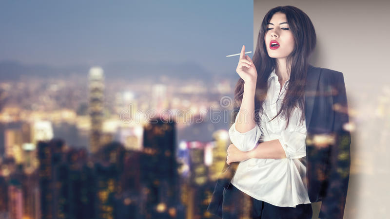 Woman smoking on balcony in night city. Young fashion model smoking on balcony at night asian city illuminated street royalty free stock photography