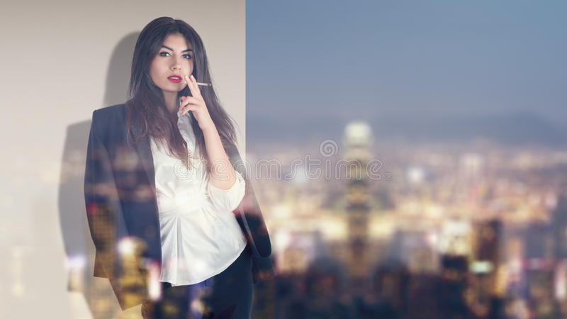 Woman smoking on balcony in night city. Young fashion model smoking on balcony at night asian city illuminated street royalty free stock images
