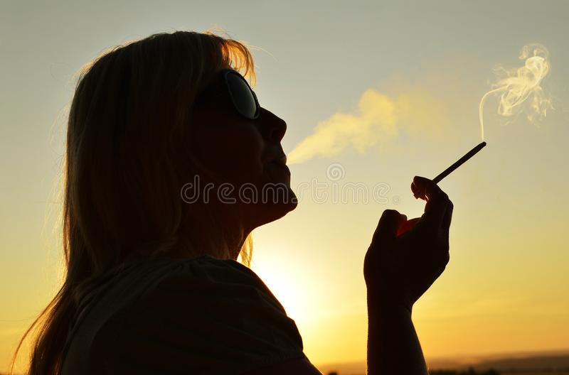 Woman smoking a cigarette. stock images