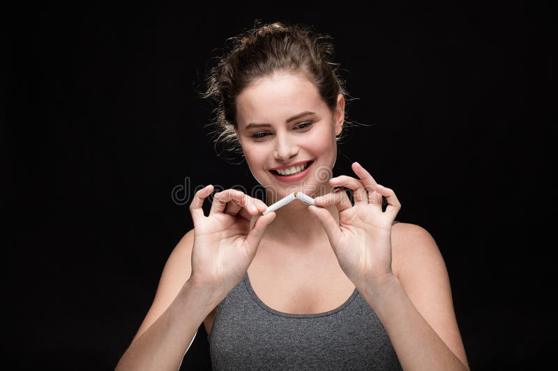 Woman smoking concept on black. Young woman breaking a cigarette, smoking concept on black background royalty free stock image
