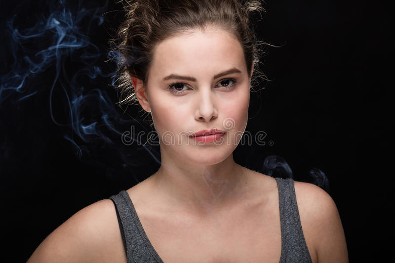 Woman smoking concept on black. Young woman with cigarette, smoking concept on black background royalty free stock image