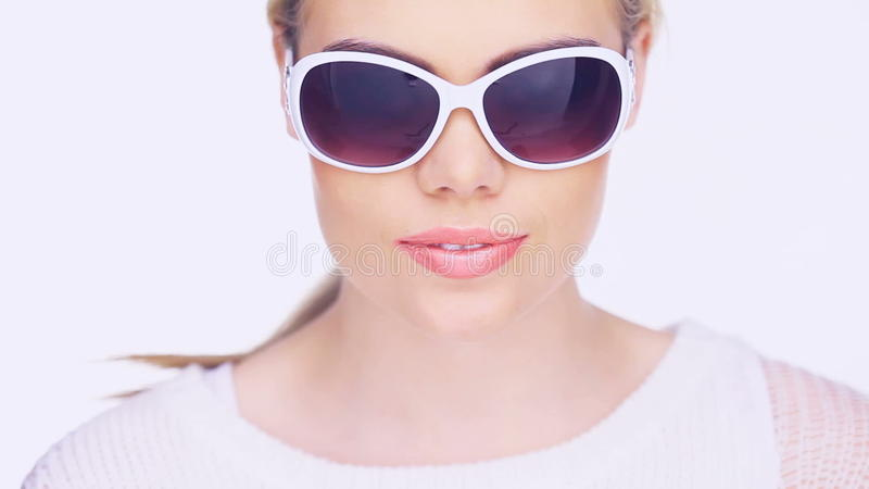 Woman smoking an e-cigarette. Woman in trendy stylish glasses smoking an e-cigarette puffing out a cloud of smoke at the camera isolated on white stock video