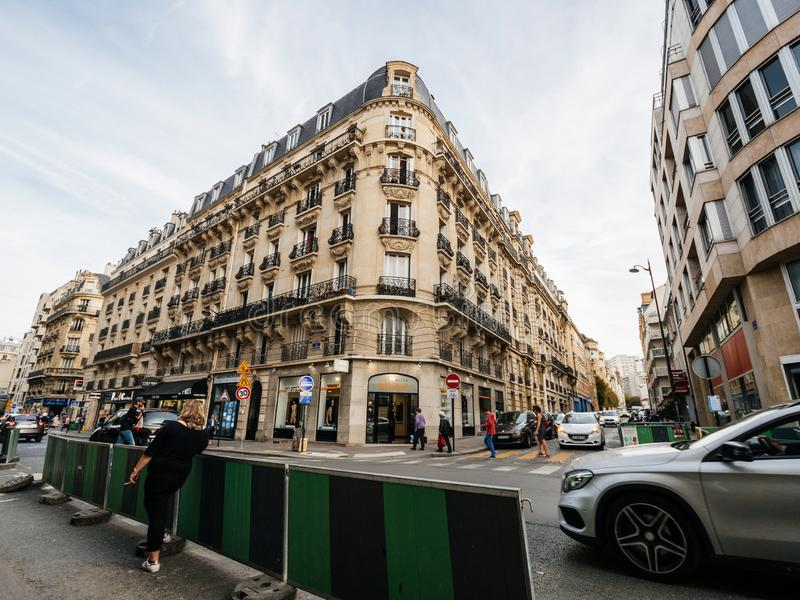 Woman smoking on a Paris street. PARIS, FRANCE - OCT 13, 2018:Woman smoking on the corner of the street with Hausmannian building in the background royalty free stock images