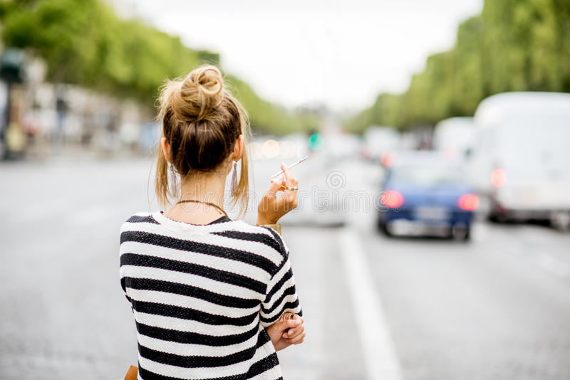 Woman smoking on the street. Young stylish woman in striped sweater with eyeglasses smoking a cigarette standing back outdoors on the street in Paris royalty free stock photography