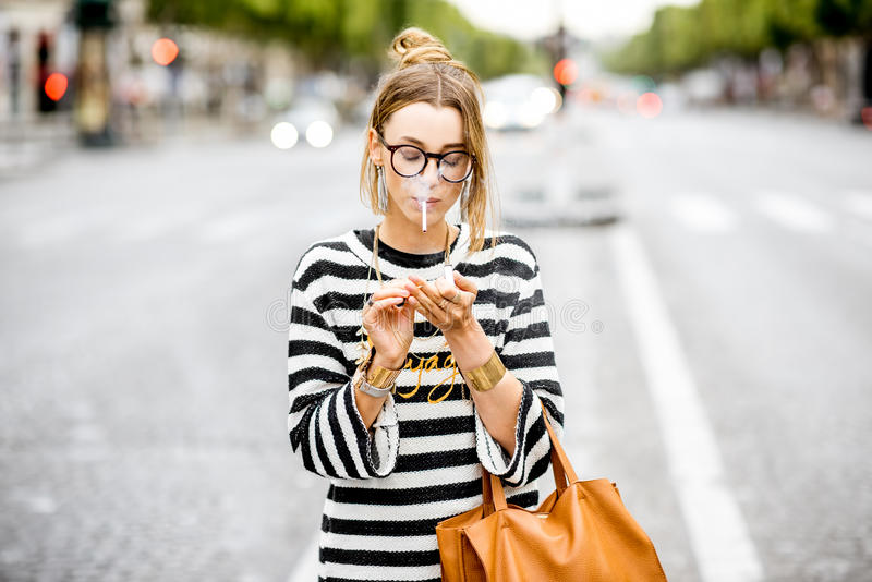 Woman smoking on the street. Young stylish woman in striped sweater with eyeglasses smoking a cigarette standing outdoors on the street in Paris royalty free stock photo