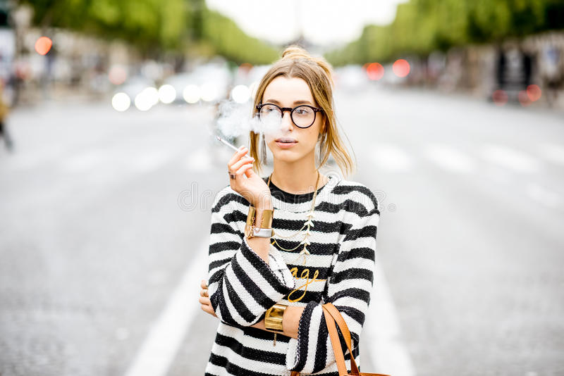 Woman smoking on the street. Young stylish woman in striped sweater with eyeglasses smoking a cigarette standing outdoors on the street in Paris stock images