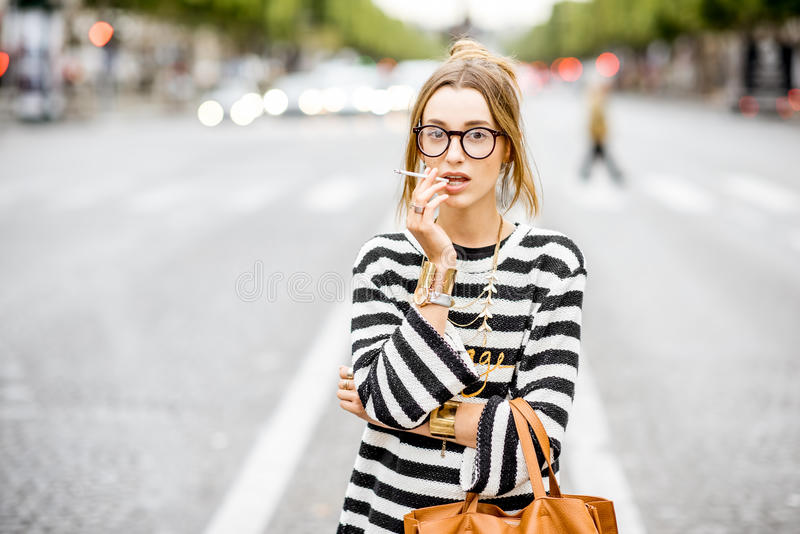 Woman smoking on the street. Young stylish woman in striped sweater with eyeglasses smoking a cigarette standing outdoors on the street in Paris royalty free stock photos