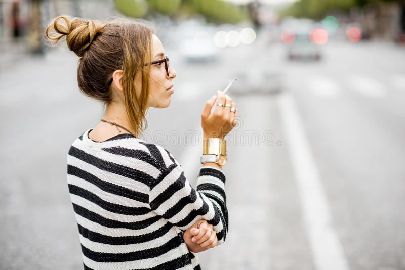 Woman smoking on the street. Young stylish woman in striped sweater with eyeglasses smoking a cigarette standing outdoors on the street in Paris stock photography