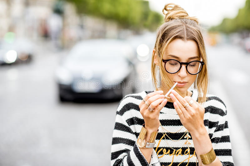 Woman smoking on the street. Young stylish woman in striped sweater with eyeglasses smoking a cigarette standing outdoors on the street in Paris stock photos