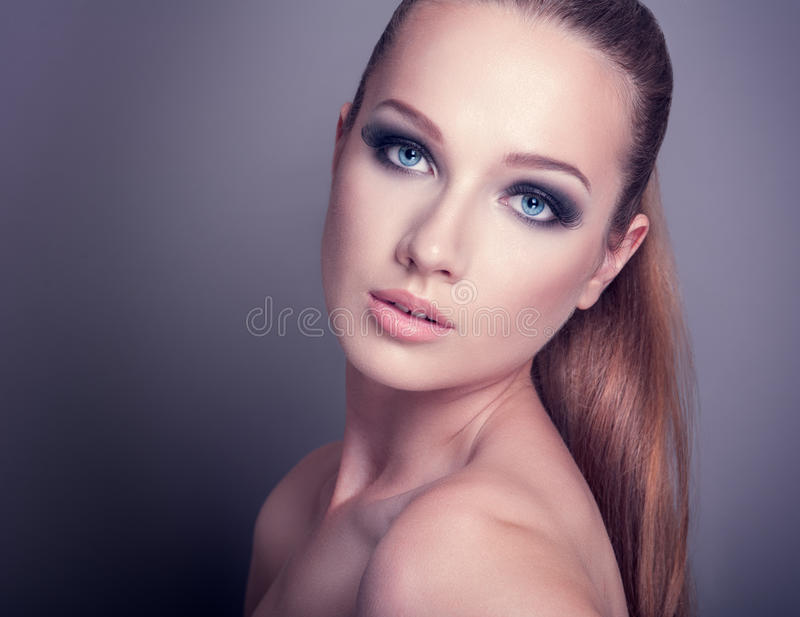 Woman with smoky eye. Beautiful woman on a dark background with smoky eye makeup stock photos