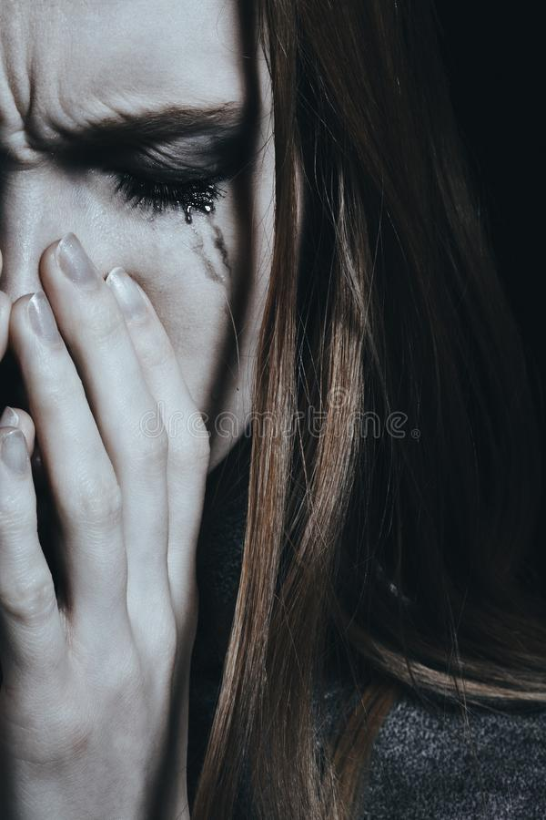 Woman with smudged makeup. Violence victim woman with smudged makeup being scared and hurt stock photo