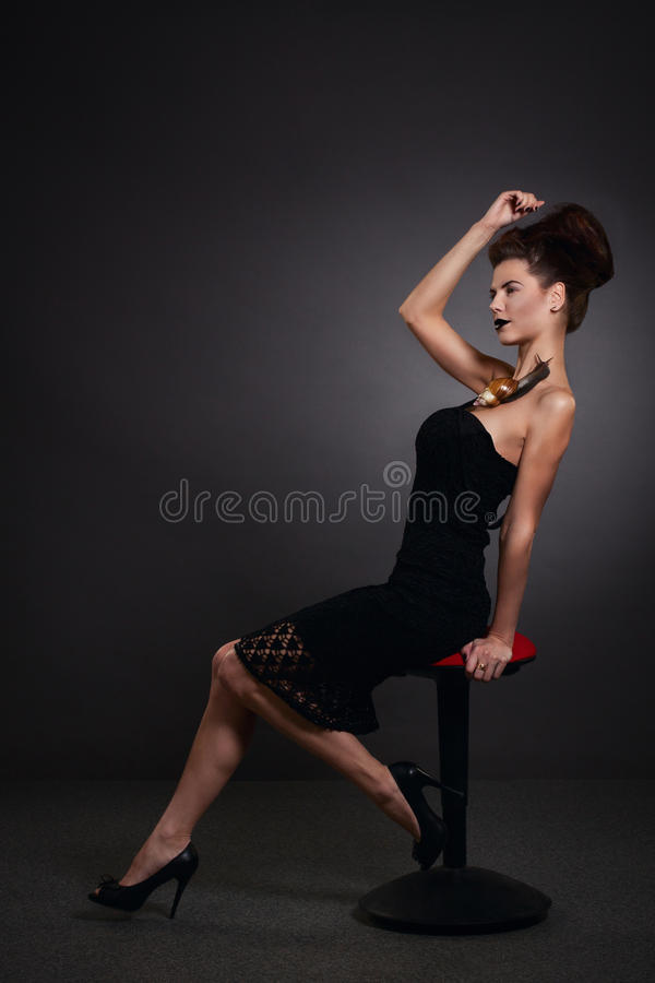 Woman with snail in black dress. Fashion. Gothic. Woman with snail on the shoulder in black dress in Gothic Halloween image royalty free stock photography