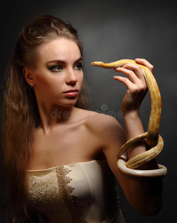 Woman with snake. Portrait of young woman with yellow snake on dark background stock image