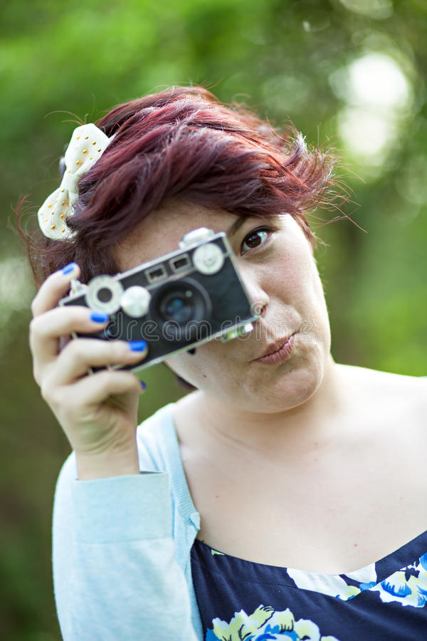 Woman Snapping a Photo. Female Photographer Shooting a vintage slr camera outdoors stock photos