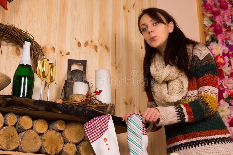 Woman Sneaking a Peek inside Christmas Stocking. Woman Wearing Sweater Sneaking a Peek inside Christmas Stocking royalty free stock photos