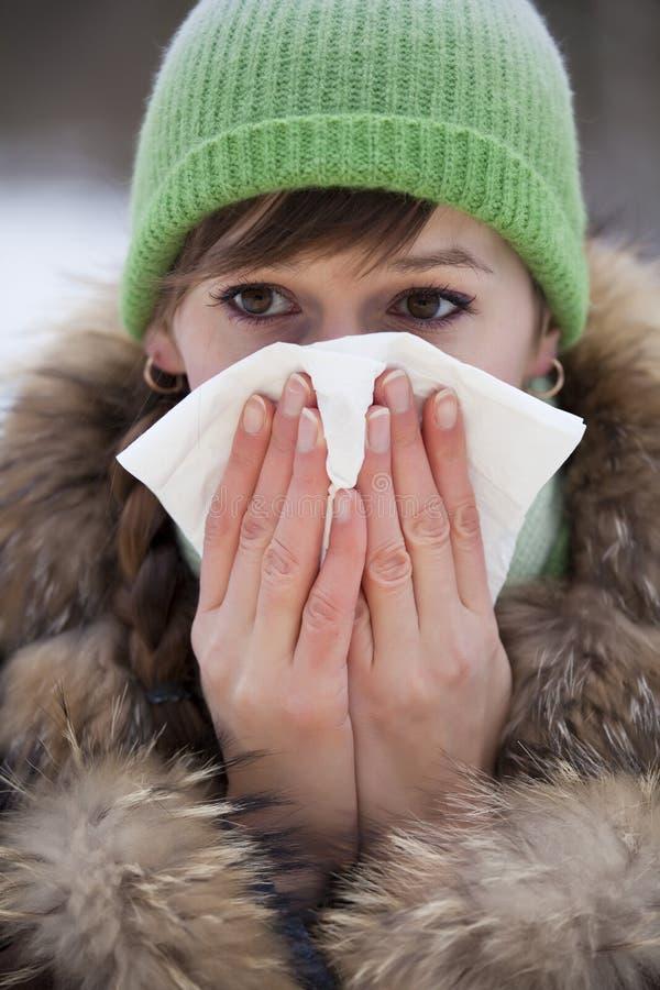 Woman sneezing in handkerchief