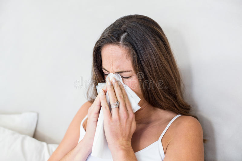 Woman sneezing with tissue on mouth royalty free stock photography