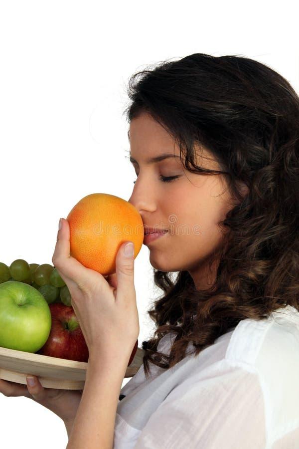 Woman sniffing orange