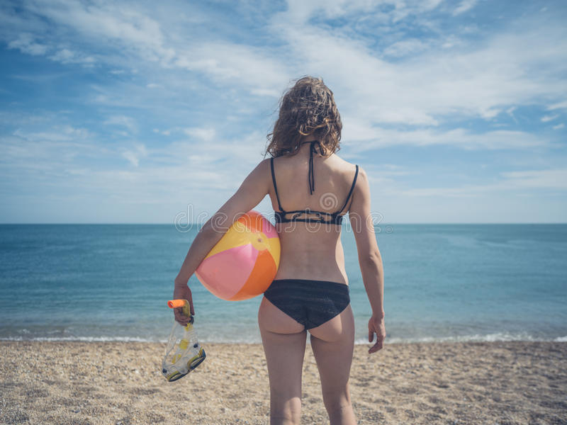Woman with snorkel and beach ball. A young woman is standing by the sea with a snorkel and a beach ball stock photography