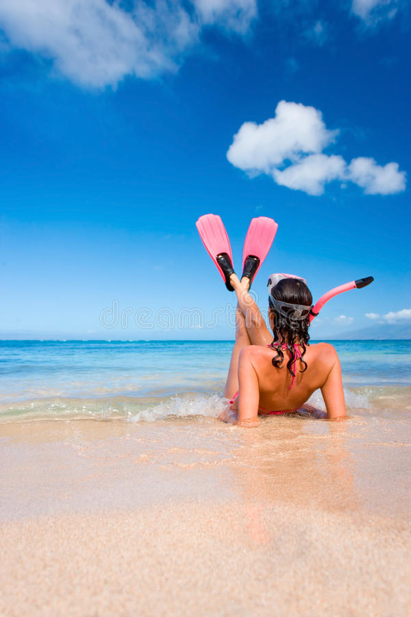 Woman snorkel flippers on beach. Woman in pink snorkel gear on sandy beach royalty free stock photos