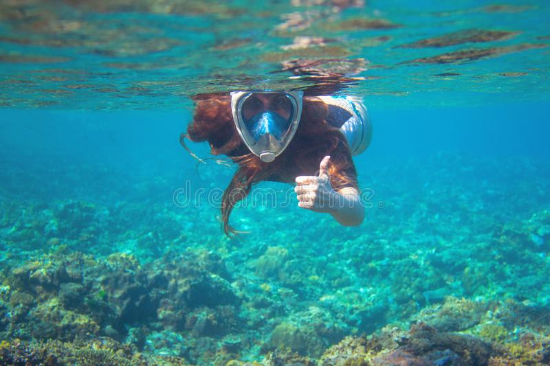 Woman in snorkel mask show thumb up underwater. Snorkeling in tropical sea coral reef. Girl in full-face snorkeling mask stock photography