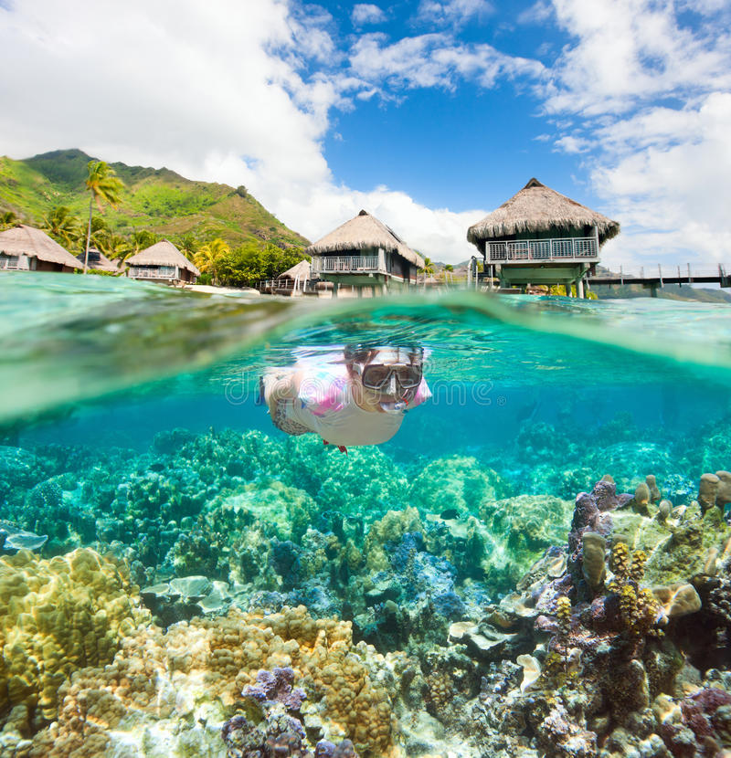 Woman snorkeling at coral reef. Woman snorkeling in clear tropical waters in front of overwater bungalows royalty free stock photos