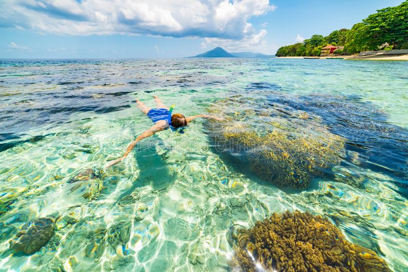 Woman snorkeling on coral reef tropical caribbean sea, turquoise blue water. Indonesia Banda archipelago, Moluccas Maluku, tourist royalty free stock photography