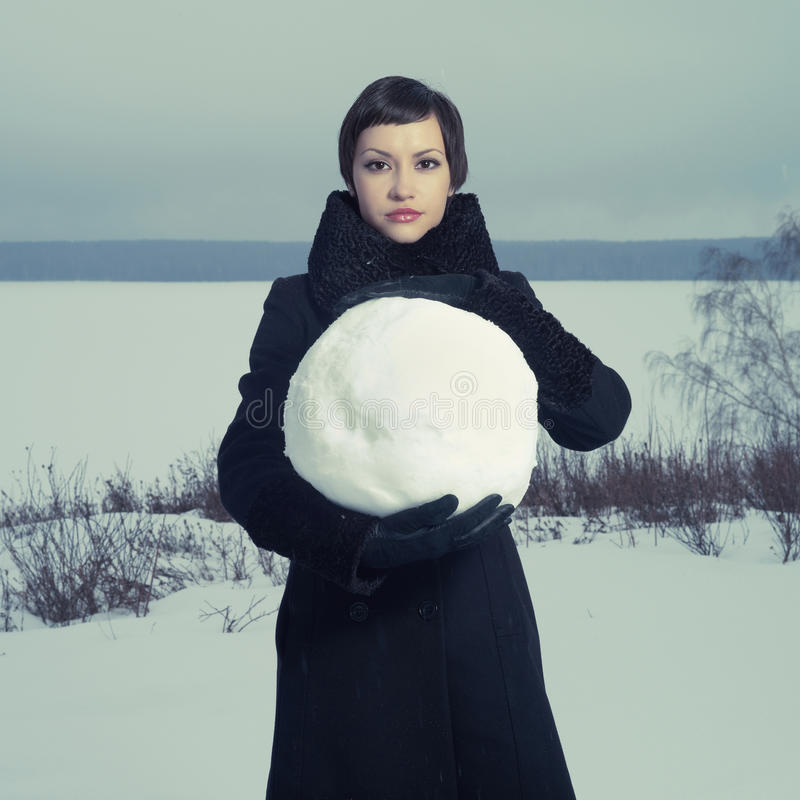 Woman with snow ball. Portrait of a young girl with a big snow ball royalty free stock image