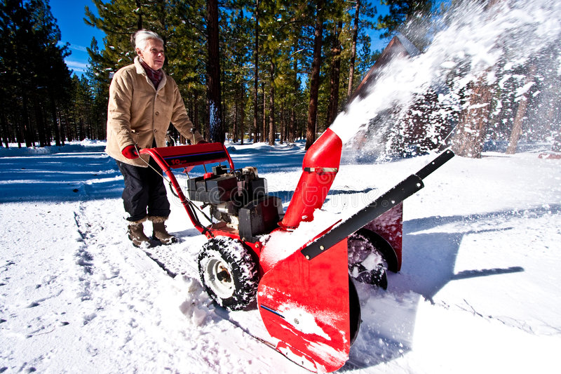 Woman snow blowing stock image
