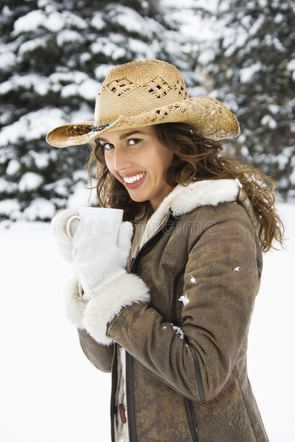 Woman in snow holding coffee. stock photos