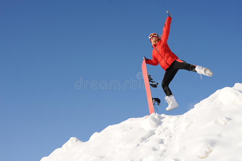Woman with snowboard. Jump of happy young woman with snowboard royalty free stock image