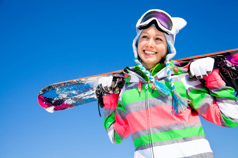 Woman with snowboard. Portrait of young smilling woman with snowboard on ski holiday in mountains stock images