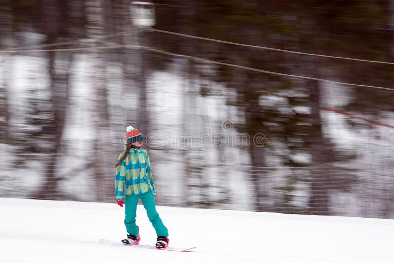 Woman on snowboard riding. Woman in colorful outwear in motion of riding snowboard down snowy slope of mountain stock photography