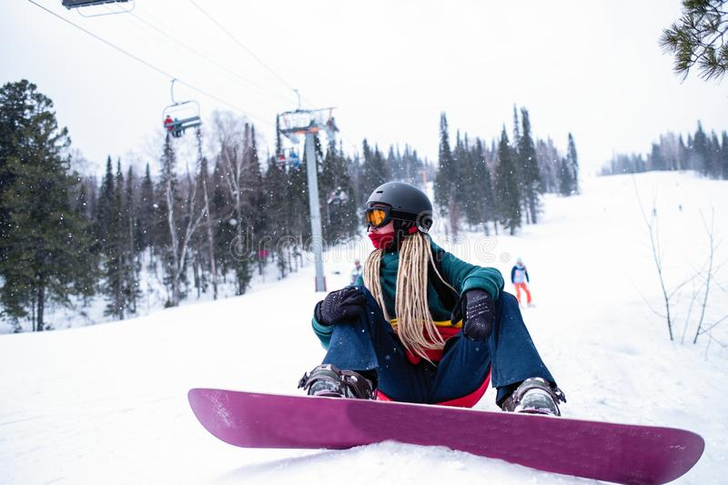 Woman snowboarder with dreadlocks it sitting with a snowboard on the ski slopes. Sport. royalty free stock photo