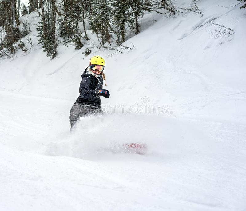 Woman snowboarder in motion in mountains royalty free stock photos