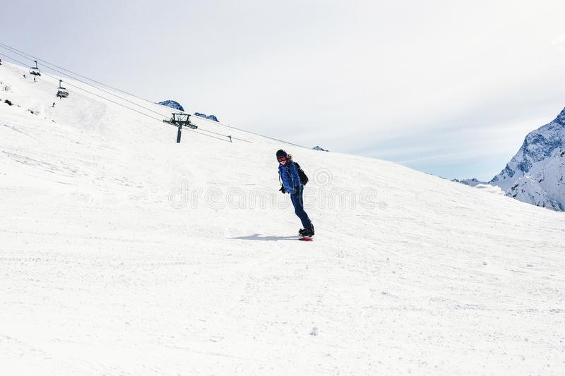 Woman snowboarder on a slope winter stock image