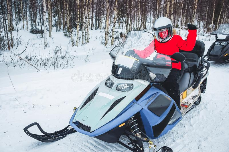 Woman in Snowmobile in Winter Finland, Lapland at Christmas. Extreme Sport Activity and Recreation in Cold Season. Drive a Snow royalty free stock photos
