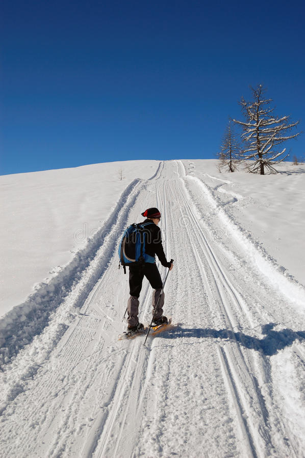 Woman snowshoeing stock photo