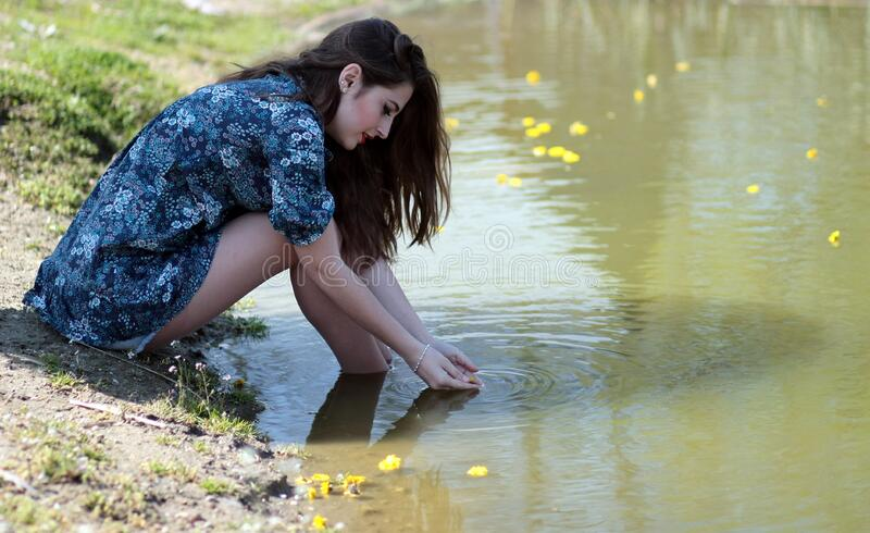 Woman Soaking Her Feet on Body of Water during Daytime stock photo