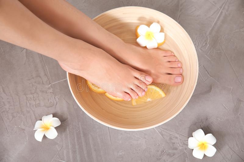 Woman soaking her feet in bowl with water, orange slices and flower on grey background, top view royalty free stock photo
