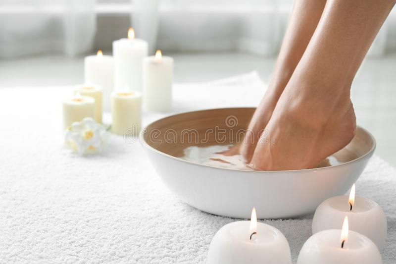 Woman soaking her feet in dish indoors, closeup with space for text. stock photo