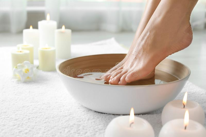 Woman soaking her feet in dish indoors, closeup with space for text. stock image