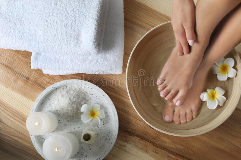 Woman soaking her feet in dish with water and flowers on wooden floor, top view. royalty free stock photography